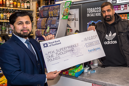 Shazhad receiving a cheque for £1,000 from his Handepay advisor.